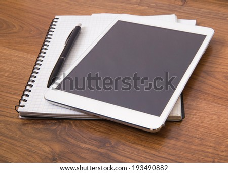 Blank modern digital tablet with papers and pen on a wooden desk.