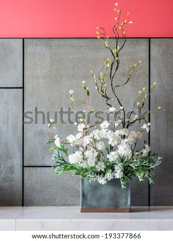 Blank modern interior wall with artificial flowers in ceramic vase