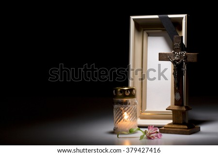 blank mourning frame with crucifix, flower and candle on dark background - stock photo