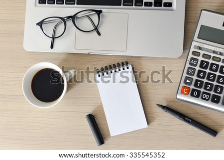Blank Note Pad, Calculator, Computer, Pen on the Table - taken in natural light to create realistic indoor mood