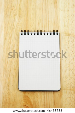 Blank note pad on wooden background