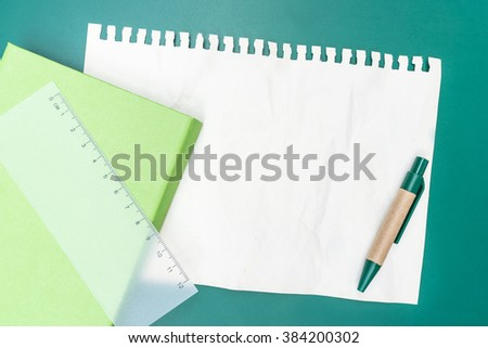 Blank note paper crumpled with pen ruller and green background - stock photo