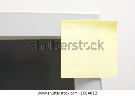 Blank note sticked on the side of a monitor - stock photo