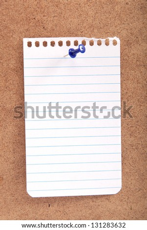 Blank note with button on a wooden board.