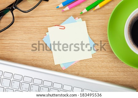 Blank note with office supplies and coffee cup on wooden table. Above view - stock photo