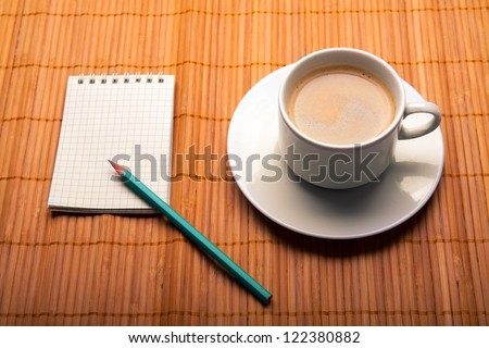blank notebook and coffee cup on wooden background - stock photo