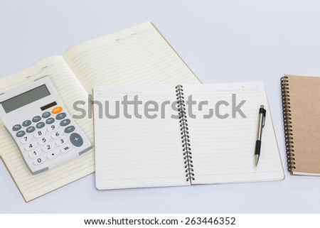 Blank notebook and office accessories on white table