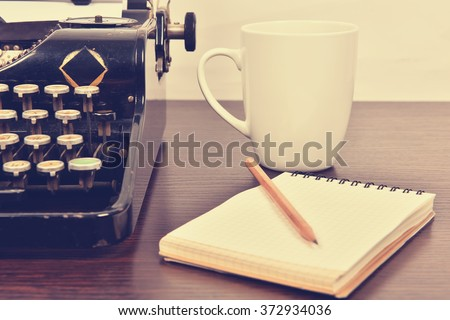blank notebook, cup and  vintage typewriter  on the writer's desk - stock photo