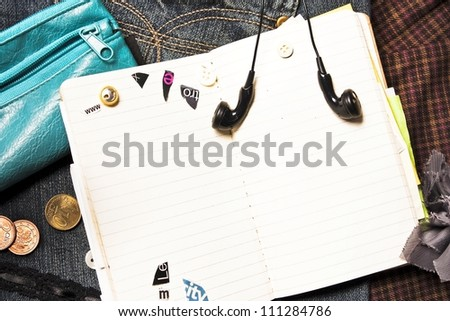 Blank notebook for personal entries, ear-phones and purse - stock photo