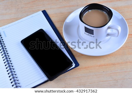 Blank Notebook, fountain pen, smartphone and cup of coffee on work desk