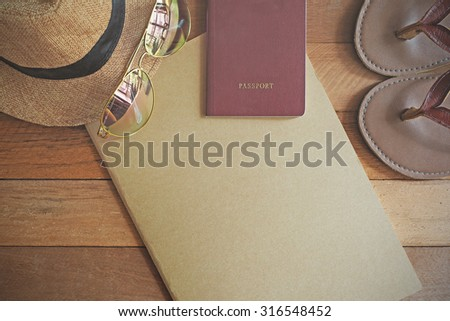 Blank notebook, hat, sunglasses, passport and flip flops on wooden background. Travel concept. Vintage effect. - stock photo