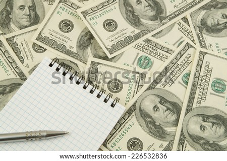 Blank notebook on dollar banknotes background