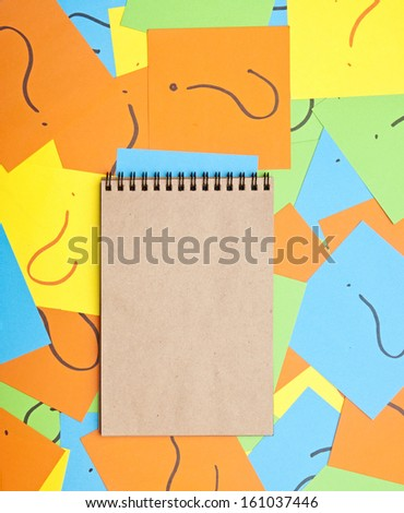 blank notebook on pile of colorful paper notes with question marks  - stock photo