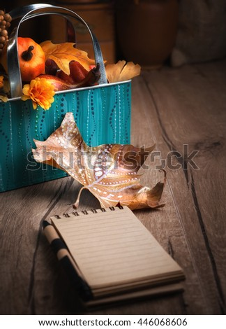 Blank notebook on wooden table on the vintage kitchen with Autumn decorations. Shallow DOF, focus on the autumn leaf. Space for your caption on the page. This image is toned - stock photo