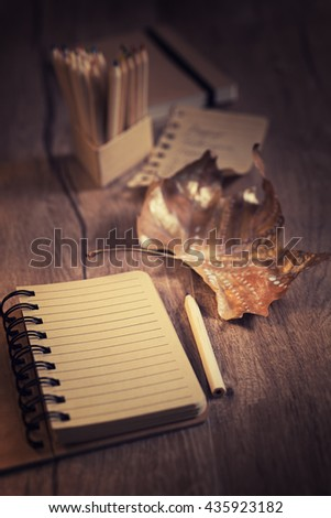 Blank notebook  on wooden table on the wintage kitchen with Autumn decorations. Text space. Shallow DOF, focus on the page. This image is toned - stock photo