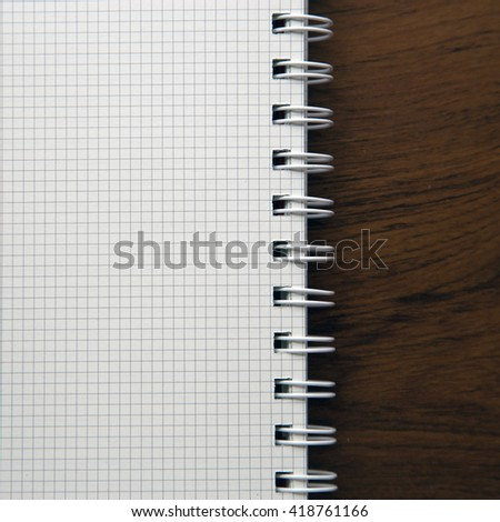 Blank notebook paper on wooden desk background
