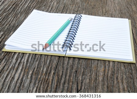 Blank notebook sand pencil on wood background