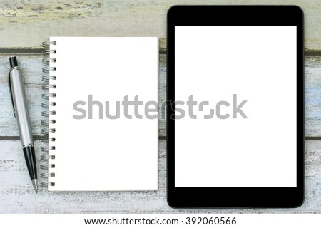Blank notebook with a silver pen next to black tablet computer with white blank screen