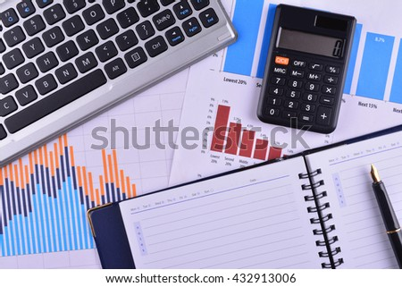 Blank Notebook with calculator, keyboard and fountain pen on graphs, charts and business table. The workplace of business people - stock photo