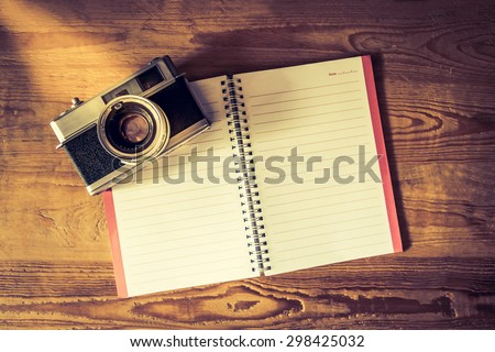 Blank notebook with fountain pen and retro camera on wooden table vintage style - stock photo
