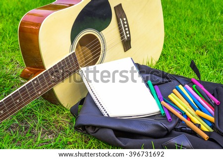 Blank notebook with pen and guitar on Green Grass background. - stock photo