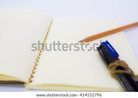 Blank notebook with pen and pencil - stock photo