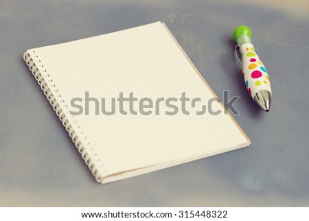blank notebook with pen and pencil on wooden table, business concept - stock photo