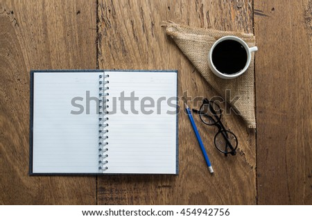 Blank notebook with pencil and coffee on table background copy space