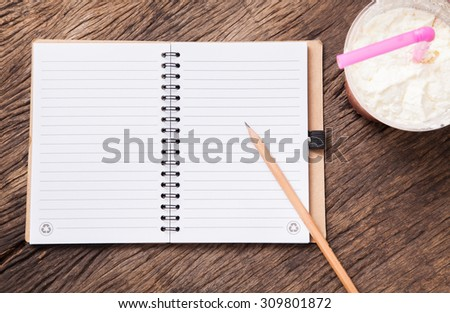 blank notebook with pencil and takeaway cup of cocoa milkshake on wooden table top.