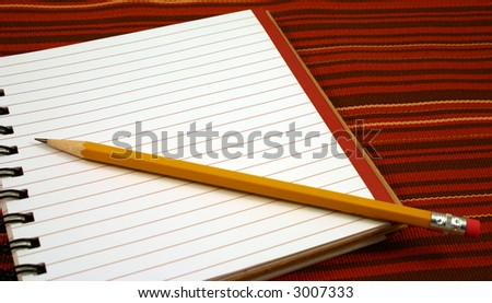 Blank notebook with pencil on a tablecloth.