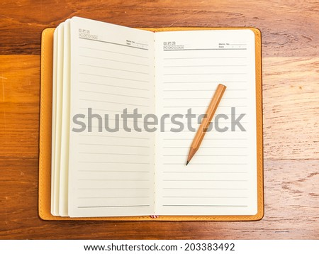 Blank notebook with pencil on office table - stock photo