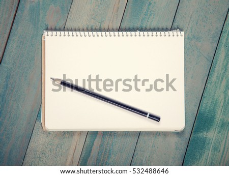 Blank notebook with pencil on wooden baclground