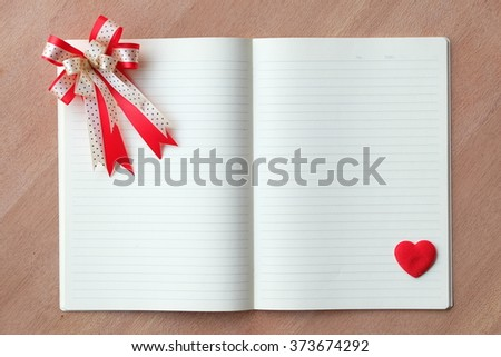 blank notebook with red heart and ribbon on wood textures  - stock photo