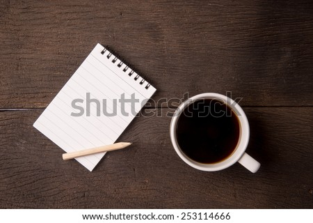 Blank notepad and coffee cup on office wooden table - stock photo