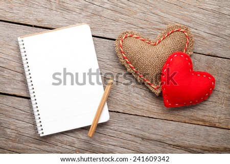 Blank notepad for copy space and vintage handmaded valentines day toy hearts over wooden background - stock photo