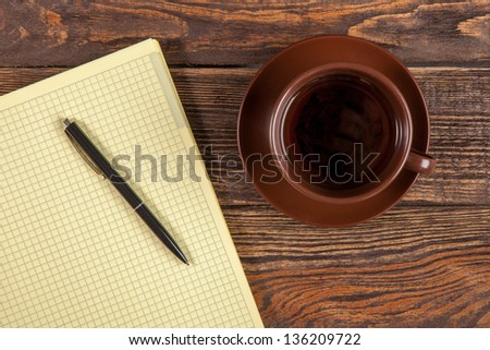 Blank notepad on a wooden table - stock photo