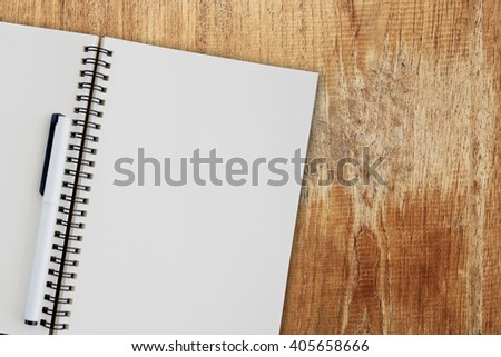Blank notepad on wooden table. - stock photo