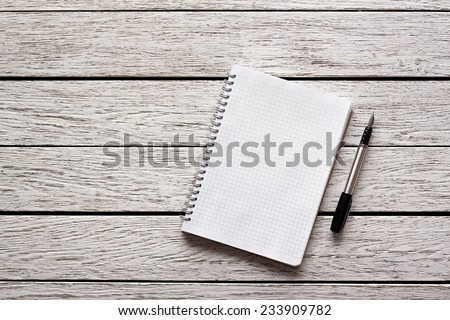 Blank notepad with a pen on white wooden desk. - stock photo