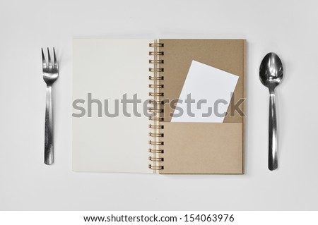 Blank notepad with fork and a piece of paper on white background - stock photo