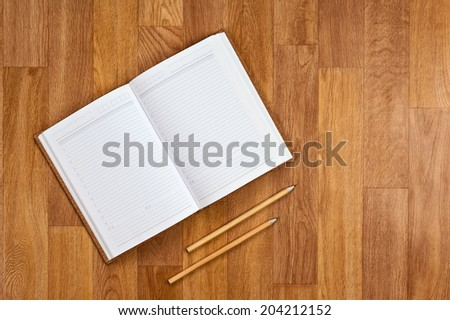 Blank notepad with office supplies on wooden table. Above view. - stock photo