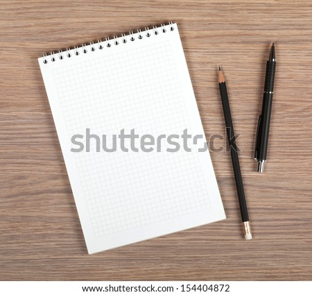 Blank notepad with pen and pencil on office wooden table - stock photo
