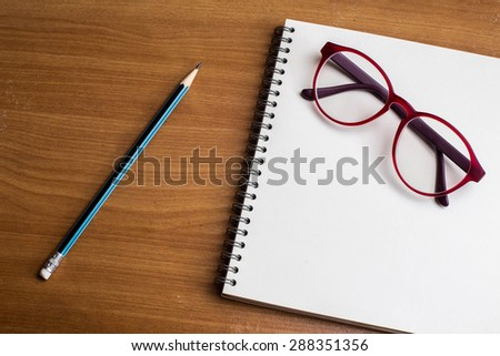 Blank notepad with pen, glasses and pencil on office wooden table. - stock photo