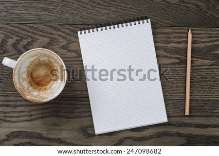 Blank notepad with pencil and empty coffee cup on wooden table, office theme