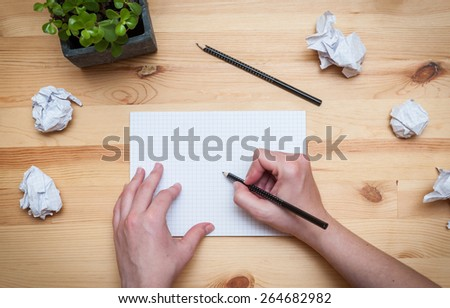 Blank notepad with pencil and flower on wooden desk - stock photo