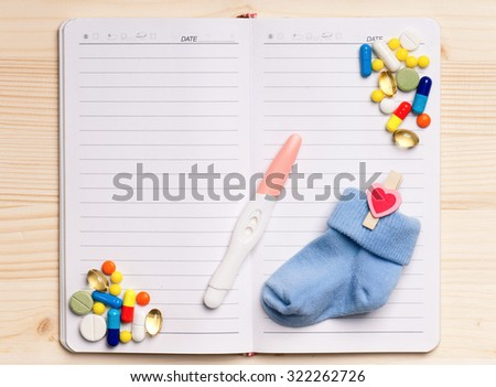 Blank notepad with pregnant test on the wooden table. View from above - stock photo