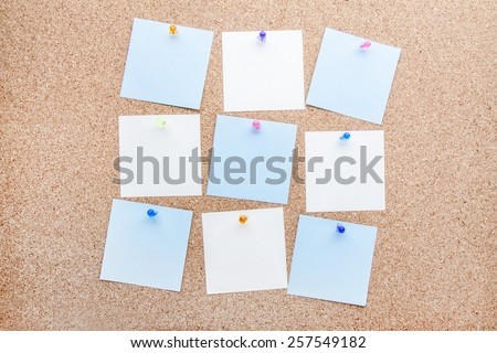 blank notes and multicolored thumbtacks on brown cork board  - stock photo