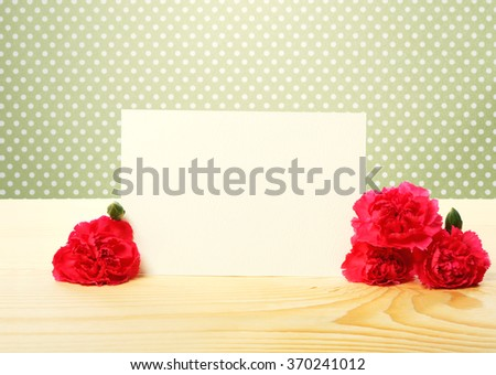 Blank Off White Greeting Card with Attractive Carnation Flowers on Top of a Wooden Table with Green Polka Dots Background - stock photo
