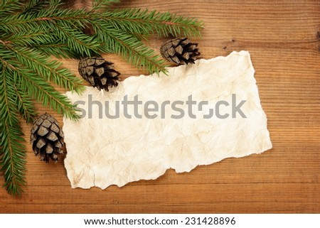 Blank Old Paper Sheet with Christmas tree branches and cones on wooden background - stock photo