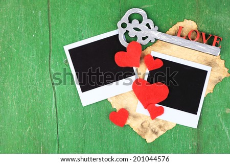 Blank old photos and decorative key, hearts on color wooden background - stock photo