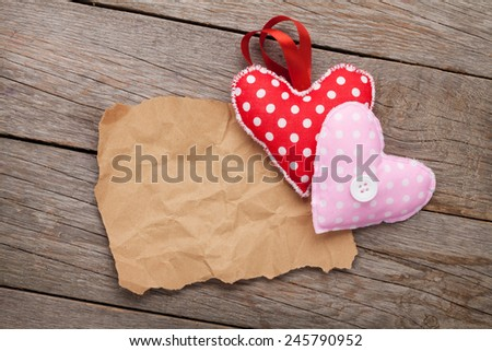 Blank old piece of paper and vintage handmaded valentines day toy hearts over wooden background - stock photo